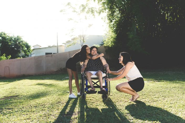 A woman in a wheelchair being hugged by a young girl and holding the hand of a young woman