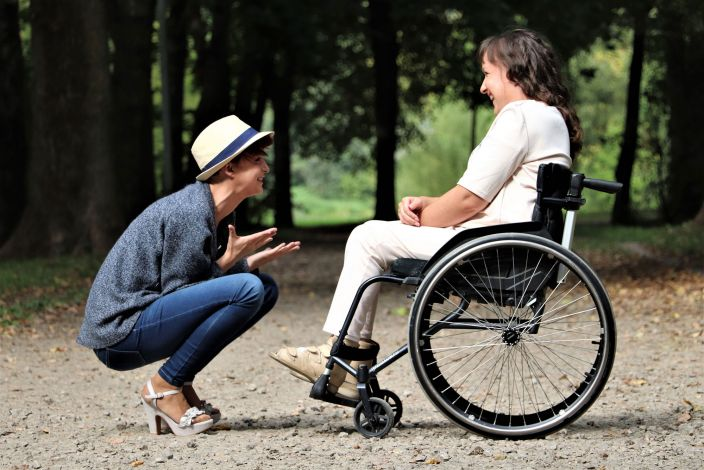 Person wearing a hat and high-heeled sandals, crouching down in front of woman in wheelchair