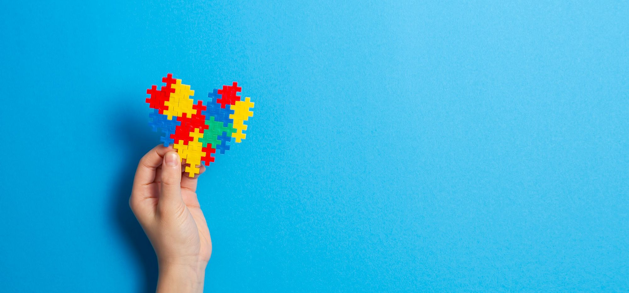 Hand holding a puzzle heart, autism awareness